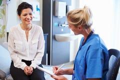 Kvinnligt patient- och för doktor Have Consultation In sjukhusrum royaltyfria foton