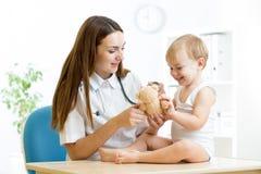 Kvinnligt pediatriskt undersöka av barnet i sjukhus Arkivbilder