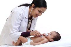 Kvinnligt pediatriskt undersöker nyfött behandla som ett barn arkivfoton