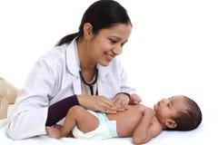 Kvinnligt pediatriskt undersöker nyfött behandla som ett barn arkivfoto