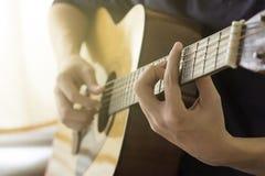 Kvinnligt räcka den leka akustiska gitarren Royaltyfria Bilder