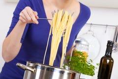Kvinnligt räcker att lyfta lagad mat pasta ut ur krukan Fotografering för Bildbyråer
