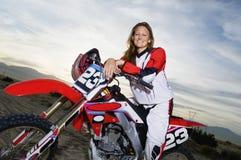 Kvinnligt racerbilsammanträde på motorcykeln mot molnig himmel arkivbilder