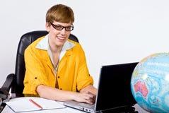 Kvinnligt sammanträde bak ett skrivbord i ljust gult omslag Royaltyfri Fotografi