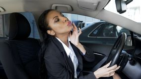 Kvinnligt sammanträde för härlig affär i lyxigt auto och se i spegeln, glamour royaltyfri foto
