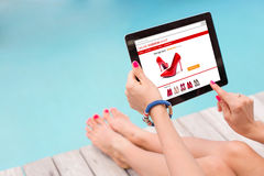 Kvinnligt sammanträde vid pölen och användateknologin för att shoppa direktanslutet Arkivfoton