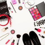 Kvinnligt skrivbord med skönhetsmedel, tillbehör och skor på vit bakgrund Lekmanna- lägenhet, bästa sikt Royaltyfri Fotografi