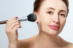 Kvinnligt smink gulligt roligt gör ha för skönhetsmedel makeupprodukter upp kvinna applicera genomskinlig fernissa för omsorgshud arkivbilder