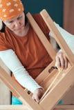 Kvinnligt snickareband som mäter trästolplatsen i seminarium royaltyfri foto