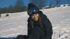 Kvinnligt snowboarder- eller skidåkaresammanträde i berg under snöfall stock video