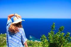 Kvinnligt stirra p? havet fr?n en kulle, medan rymma hennes hatt med hennes v?nstra hand Sk?t under dag i sommar arkivfoto