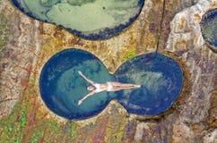 Kvinnligt sväva i det idylliska havet vaggar salighet för pöl precis arkivfoton