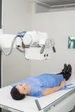 Kvinnligt tålmodigt ligga under röntgenapparaten i undersökningsrum Arkivbilder