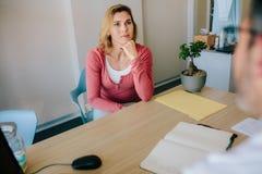 Kvinnligt tålmodigt lyssna till doktorn med koncentration royaltyfri foto