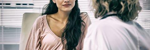 Kvinnligt tålmodigt lyssna till doktorn med koncentration i medicinskt kontor royaltyfri foto
