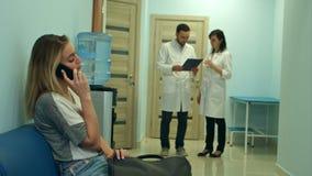 Kvinnligt tålmodigt samtal på telefonen i sjukhuskorridor medan två doktorer som konsulterar lager videofilmer