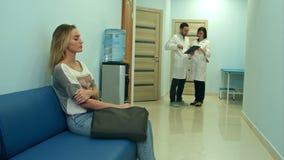 Kvinnligt tålmodigt vänta i sjukhuskorridor medan två doktorer som konsulterar stock video