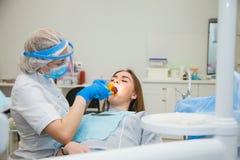 Kvinnligt tandläkarearbete med denavvänjning skyddsremsan, patient med karies på stol Arkivfoto