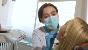 Kvinnligt tandläkarearbete, undersökande tänder av en patient på kliniken arkivfilmer