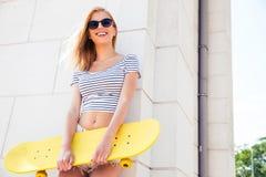Kvinnligt tonåringanseende med skateboarden Arkivbild