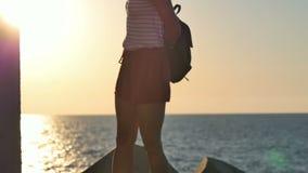 Kvinnligt turist- sätta på hennes ryggsäck på kusten stock video