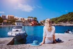 Kvinnligt turist- sammanträde på pir med blausolhatten som bakom lägger Den Assos byn med härliga traditionella hus är royaltyfria foton