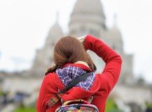 Kvinnligt turist- tagande foto av den Sacre-Coeur domkyrkan Arkivbild