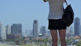 Kvinnligt turist- tagande foto av strandkusten med skyskrapor på henne telefon stock video
