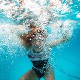Kvinnligt undervattens- med framsidan som omges av bubblor Royaltyfri Bild