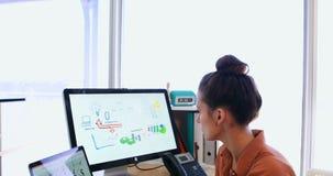 Kvinnligt utövande arbete över den grafiska minnestavlan, medan ha fruktsaft på hennes skrivbord 4k stock video