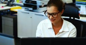 Kvinnligt utövande samtal på mobiltelefonen på skrivbordet arkivfilmer