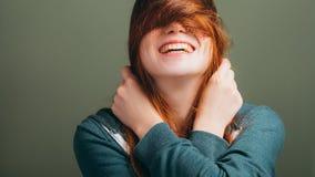 Kvinnligt uttryckande toothy leende för glädje som rör till hår royaltyfria bilder