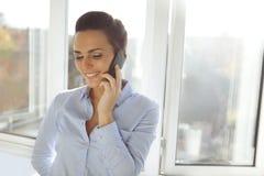 Kvinnligt utövande samtal på telefonen Arkivbild
