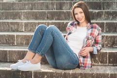 Kvinnligt vila för gladlynt hipster utanför på stentrappa royaltyfri bild
