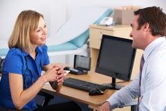 KvinnligUK-doktor som talar till den male tålmodign arkivbild