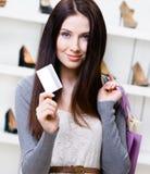 Kvinnliguppehällekreditkorten i skodon shoppar royaltyfri bild