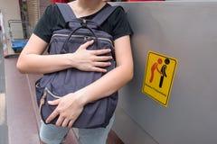 Kvinnor är den försiktiga ficktjuven, därför att hon ser akta sig ficktjuvar undertecknar symbol arkivfoton