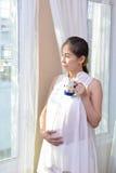Kvinnor är gravid lyckligt, när de tänker om det kommande, behandla som ett barn Arkivfoto