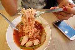 Kvinnor äter nudlar, genom att använda en gaffel för att kamma hem nudlarna arkivfoton