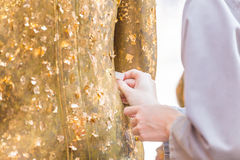 Kvinnor använder bladguldet på Buddha Royaltyfri Fotografi