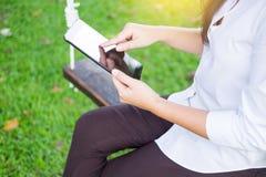 kvinnor använder minnestavlan för att arbeta, medan ligga på sunbed i trädgård arkivbilder