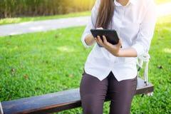 kvinnor använder minnestavlan för att arbeta, medan ligga på sunbed i trädgård arkivbild