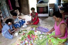 Kvinnor av Fiji som flätar blommor för hår royaltyfria bilder