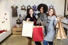 Kvinnor av olik etnicitet med shoppingpåsar som poserar i damunderkläderlager Stående av tre nätta blandras- flickor arkivfoton