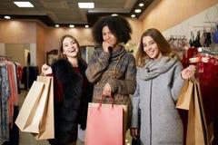 Kvinnor av olik etnicitet med shoppingpåsar som poserar i galleria Stående av tre nätta blandras- flickor som går på Arkivbilder