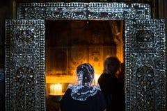 Kvinnor ber i stearinljus-tänt kapell Royaltyfri Bild
