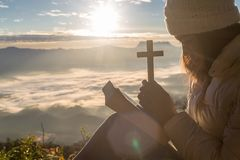 Kvinnor ber till guden med korset på bergbakgrunden med morgonsoluppgång Kvinnan ber för gud som välsignelsen till att önska har royaltyfri foto