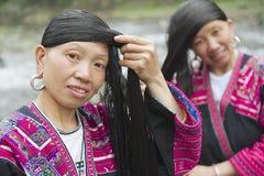 Kvinnor borstar och utformar hår i Longji, Kina Arkivbilder