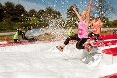 Kvinnor får besprutade med bubblor som hoppar in i skumgrop Royaltyfri Fotografi