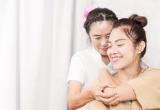 Kvinnor får hennes arm sträckt av den thailändska terapeuten Royaltyfri Bild